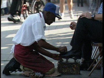 284237500-cireur-de-chaussures-s'agenouiller-la-nouvelle-orleans-trottoir